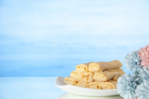 Front view yummy rolled pancakes on light-blue background milk breakfast cake dessert sweet morning flower color sugar