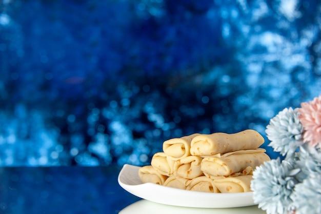 正面図紺色の背景においしいロールパンケーキ朝食ケーキ砂糖デザート朝の色ミルクフラワースウィート