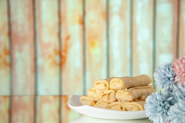 正面図明るい背景のおいしいロールパンケーキミルク朝食ケーキデザート甘い朝の花の色砂糖