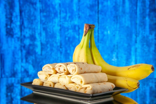 Front view yummy rolled pancakes with bananas on light-blue background morning color milk breakfast dessert sweet cake sugar