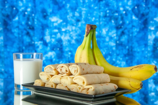 Front view yummy rolled pancakes with bananas and milk on light-blue background fruit morning sweet cake color sugar milk dessert