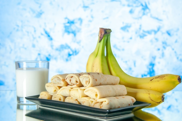 Front view yummy rolled pancakes with bananas and milk on light-blue background morning sweet cake color sugar milk dessert fruit