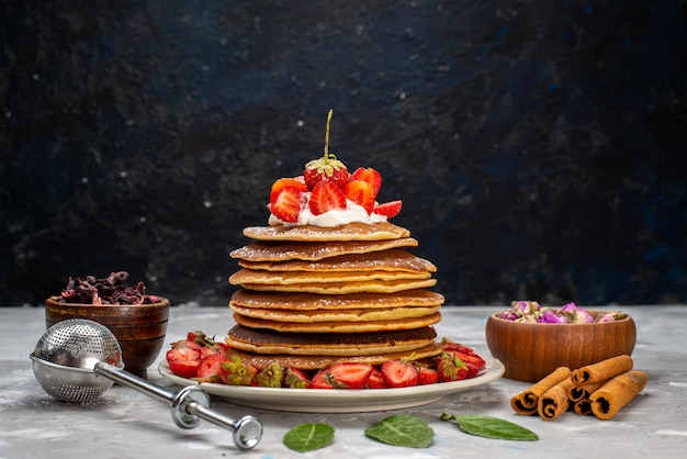 A front view yummy round pancakes with cream and red strawberries on the light desk cake