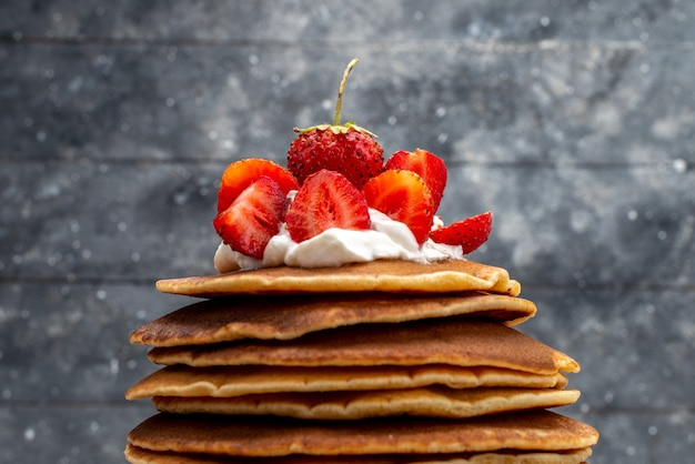 A front view yummy round pancakes with cream and red strawberries on the wooden background fruit cake