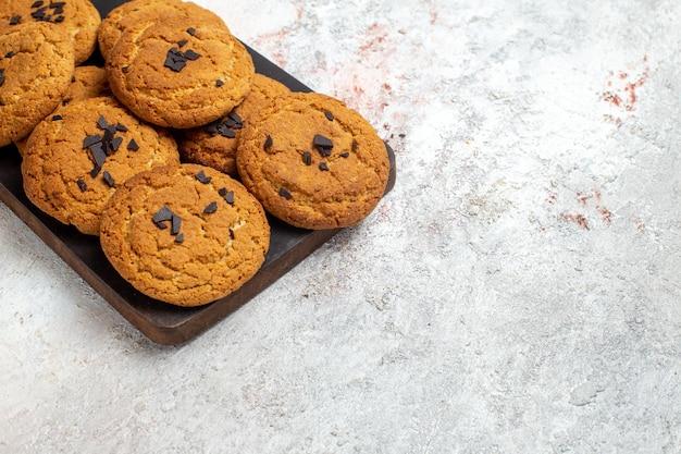 Vista frontale di deliziosi biscotti di sabbia dolci perfetti per una tazza di tè sulla superficie bianca
