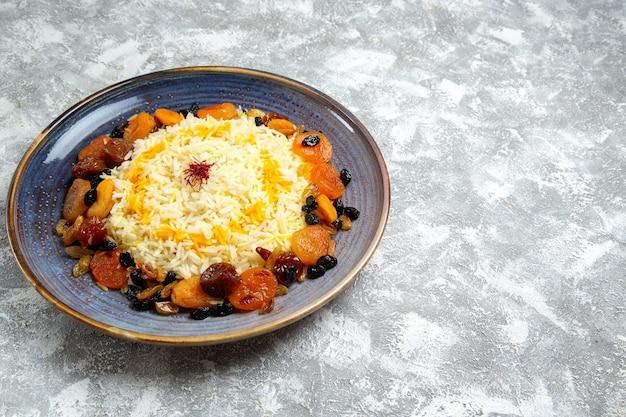 Vista frontale yummy shakh plov piatto di riso cotto con uvetta all'interno del piatto su spazio bianco