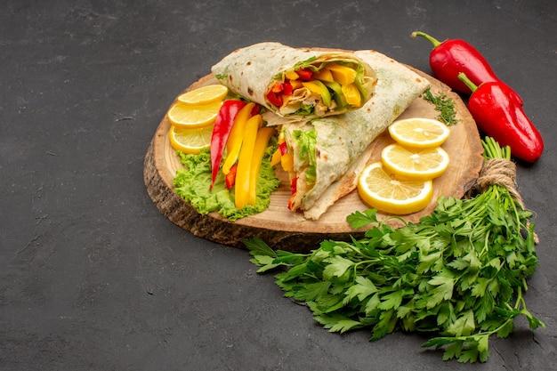 Panino di pollo affettato shaurma squisito vista frontale con limone e verdure su spazio scuro
