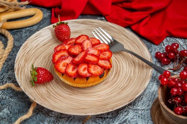 Vista frontale della gustosa torta di fragole con frutti di bosco sulla superficie scura