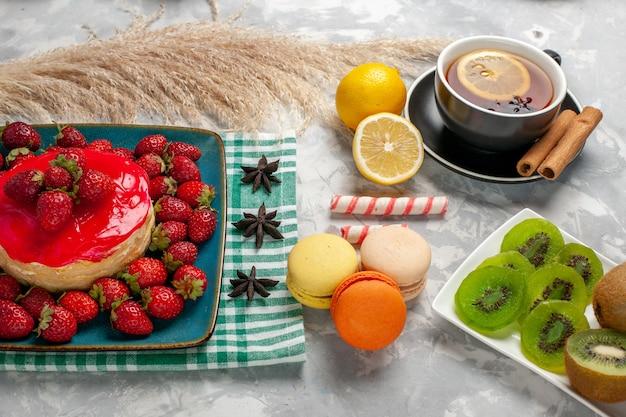 Вкусный клубничный торт, чашка чая со свежей клубникой и французские макароны на белом столе, вид спереди