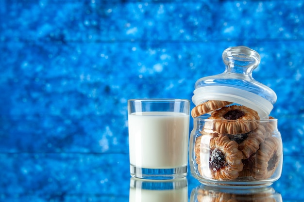 Front view yummy sweet biscuits inside can with glass of milk on a light-blue background color cookie sugar food breakfast cake morning meal