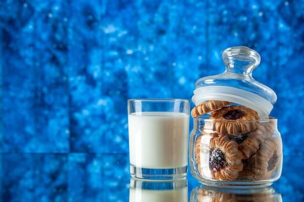 Вид спереди вкусное сладкое печенье внутри банки со стаканом молока на синем фоне цветное печенье сахар еда завтрак торт утро