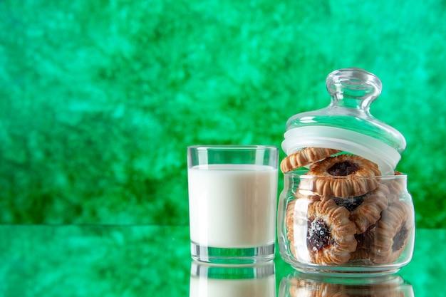 Вид спереди вкусное сладкое печенье внутри банки со стаканом молока на зеленом фоне цвет сахарный завтрак торт утренний десерт еда печенье