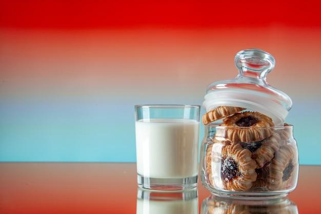 Вид спереди вкусное сладкое печенье внутри банки со стаканом молока на светло-красном фоне цвет сахарный завтрак торт утренний десерт еда печенье