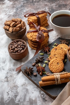Front view yummy sweet biscuits with coffee seeds and cup of coffee on a light background color cocoa sugar tea cookie sweet cake pie