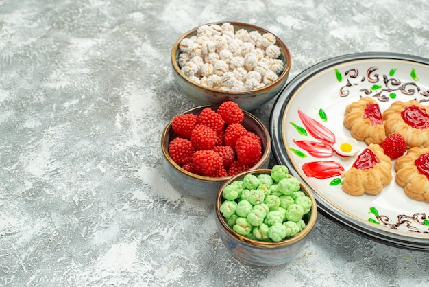 Vista frontale gustosi biscotti dolci con caramelle su spazio bianco