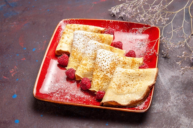 Front view yummy sweet pancakes inside red plate with raspberries on dark space