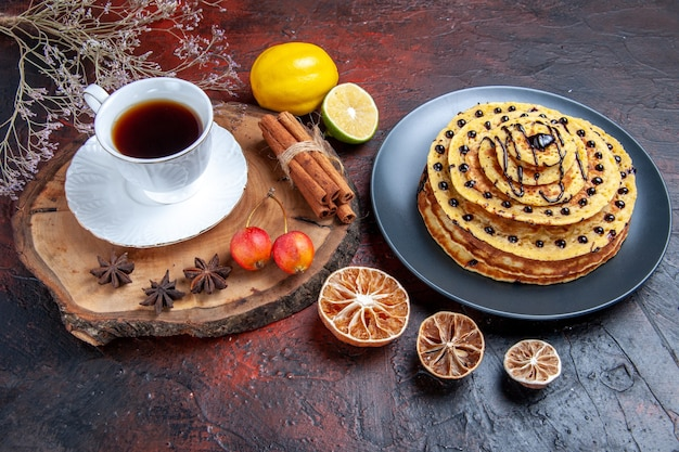 Front view yummy sweet pancakes with cup of tea on dark background cake milk sweet dessert