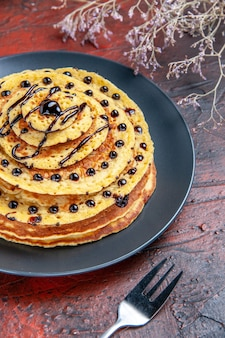 暗い床にアイシングをしたおいしい甘いパンケーキの正面図ミルクの甘いデザートケーキ