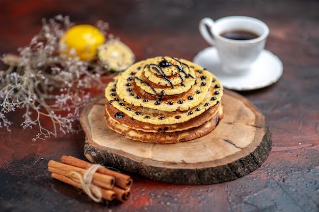暗い背景にお茶と正面図おいしい甘いパンケーキ