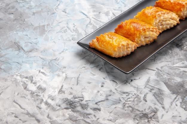 白いテーブルの上のケーキパンの中のおいしい甘いペストリーの正面図パイペストリー甘いケーキ