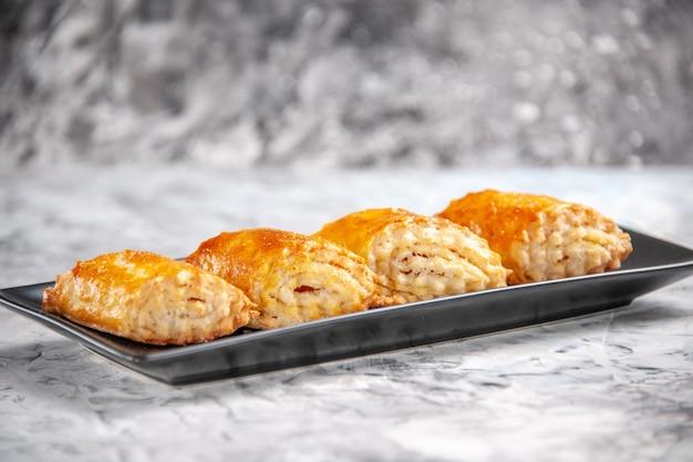 Vista frontale squisiti pasticcini dolci all'interno della tortiera su tavola bianca torta di pasticceria dolce