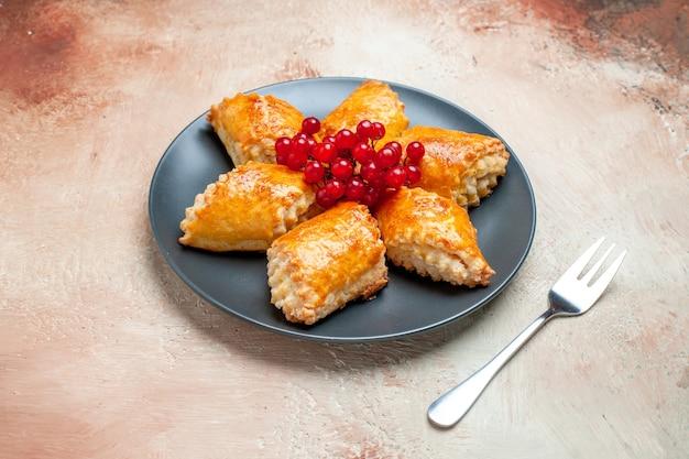 Vista frontale squisiti pasticcini dolci con frutti di bosco su tavola bianca torta torta pasticceria dolce
