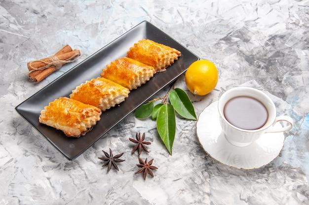 Vista frontale squisiti pasticcini dolci con tè sul tavolo bianco torta di pasticceria torta dolce