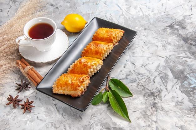 Vista frontale squisiti pasticcini dolci con tè su un tavolo bianco torte dolci torta di pasticceria