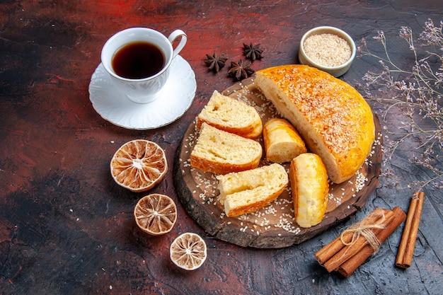 Vista frontale gustosissima pasticceria dolce con una tazza di tè su uno sfondo scuro