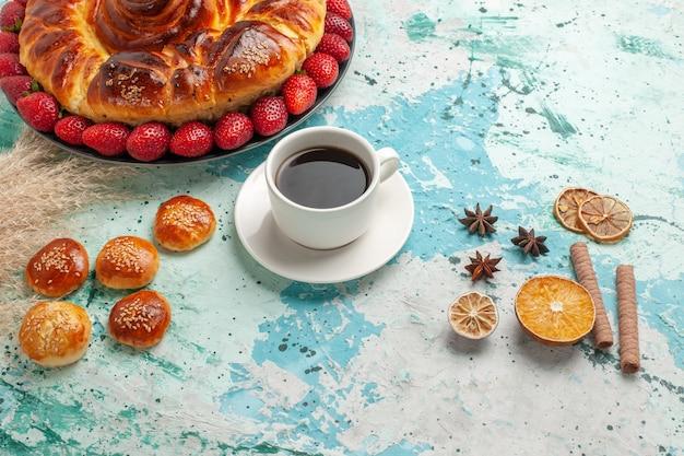 正面図新鮮な赤いイチゴと青い表面に小さなケーキとおいしい甘いパイ
