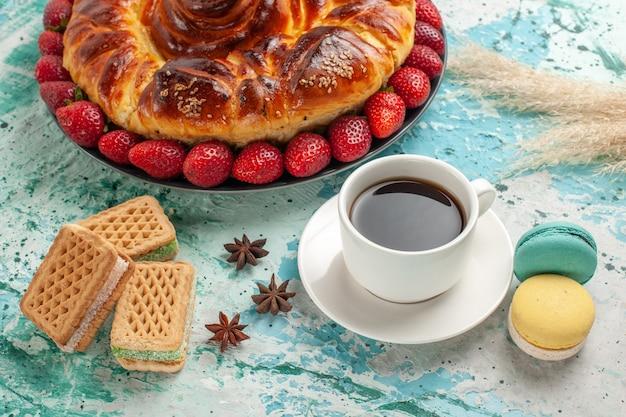 Torta dolce gustosa vista frontale con cialde di fragole rosse fresche e tazza di tè sulla superficie blu