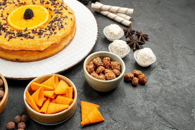 Front view yummy sweet pie with orange slices on dark-grey background dough fruit pie cake biscuit
