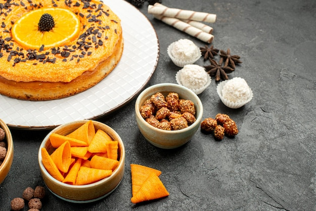 正面図濃い灰色の背景にオレンジスライスのおいしい甘いパイ生地フルーツパイケーキビスケット