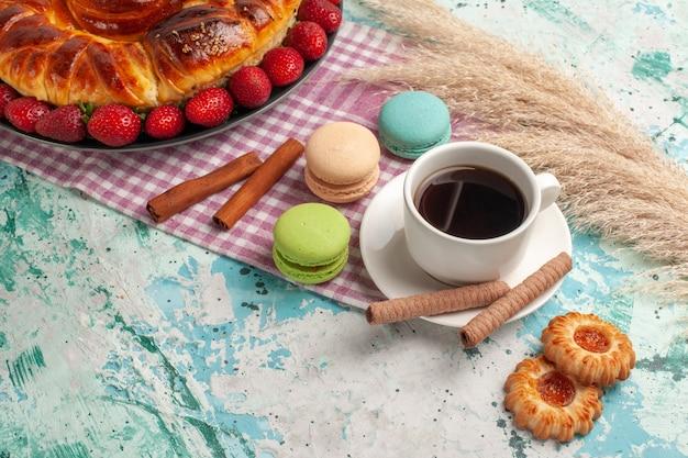 Torta dolce gustosa vista frontale con macarons francesi di fragole rosse e tè sulla superficie blu