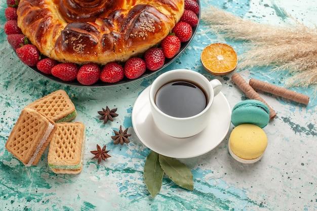 Torta dolce gustosa vista frontale con cialde di fragole e tazza di tè sulla superficie blu
