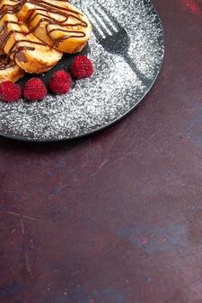 暗いスペースのプレートの中のお茶用の正面から見たおいしい甘いロールケーキ