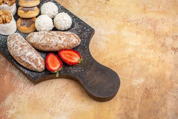 Вкусные конфеты с печеньем и конфитюрами, вид спереди на деревянном столе, сладкий пирог
