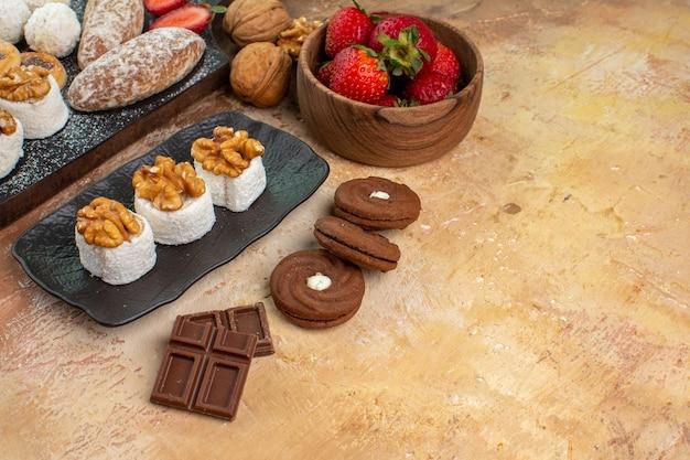 正面図木製の机の上にフルーツキャンディーとクッキーとおいしいお菓子