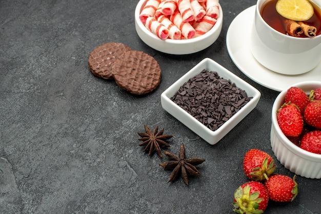 Вкусные вкусы, вид спереди, с чашкой чая, ломтиками лимонного печенья и свежими фруктами