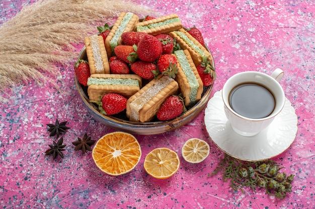 Vista frontale di gustosi biscotti waffle con fragole rosse fresche e tazza di tè