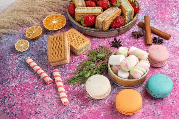 Vista frontale di gustosi biscotti waffle con fragole rosse fresche sulla parete rosa