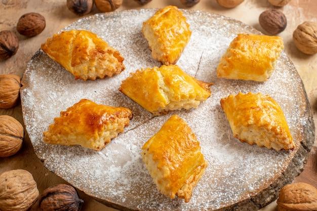 Pasticcini della noce di vista frontale yummy con le noci sulla torta dolce della pasticceria della torta del tavolo luminoso