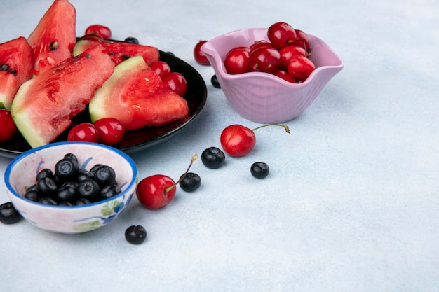 Front viewslices of watermelon on a plate with blueberries and cherries