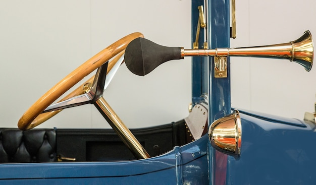 Front of a vintage blue car with an antique golden steering wheel and a separate horn