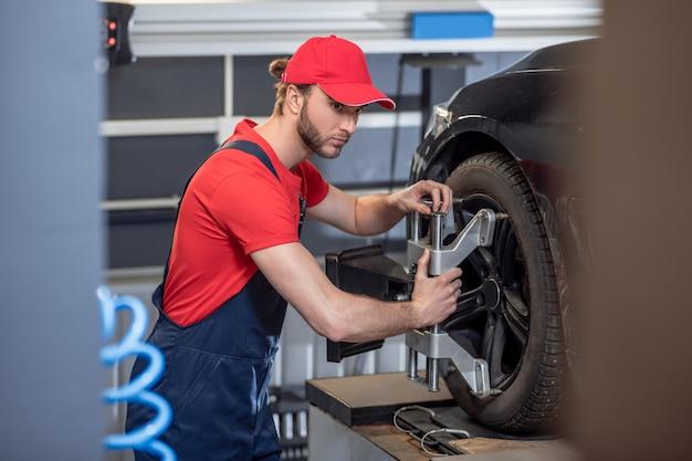 前輪、車。車のサービスで前輪の近くで専門的に働く気配りのある若い成人男性