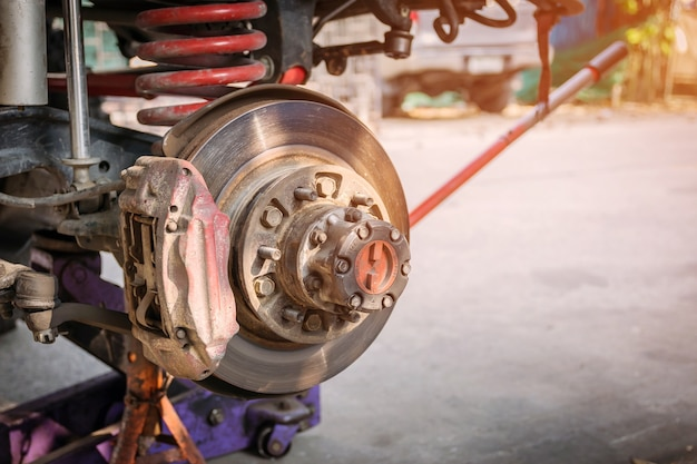 The front wheel of the car was removed to repair the brake system.
