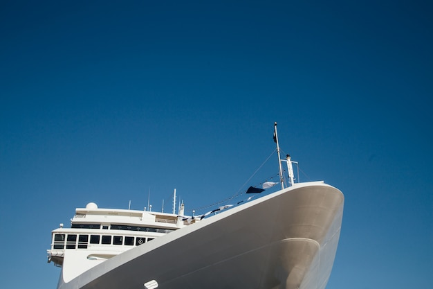 The front of a white cruise ship on a background of blue sky