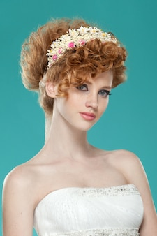 Frontal beauty portrait of a red hairred girl with hairdressed and speckle, with naked shoulders, wearing a wedding dress, over blue wall.