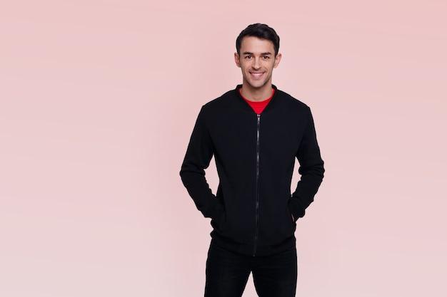 ピンクの背景に濃い青のジャンパーとジーンズの笑顔の魅力的な若いブルネットの男の正面の画像。水平方向のビュー。