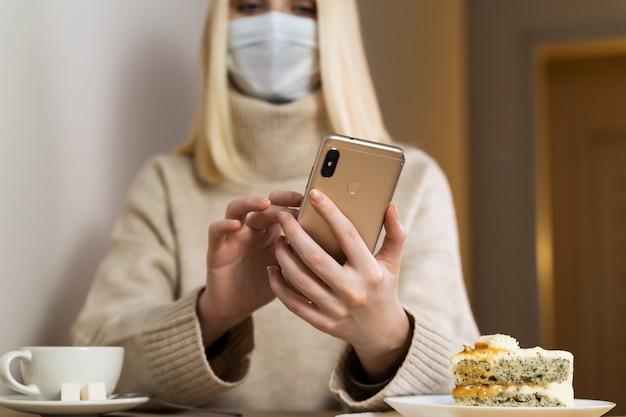 ゆるいブロンドの髪、ベージュのセーターを持つ女の子の手にある電話の正面写真